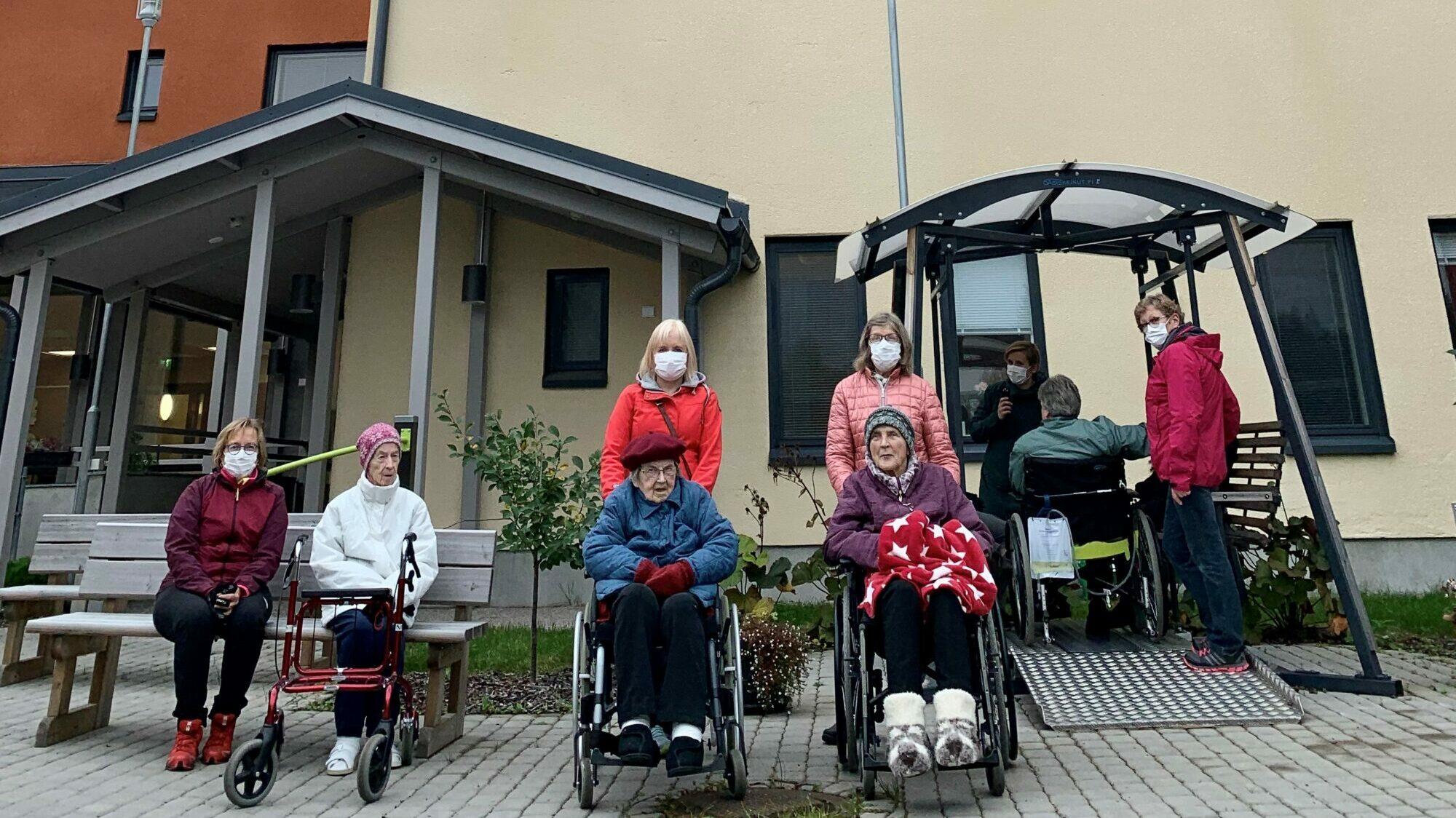 Vapaaehtoiset asiakkaiden kanssa ulkoilemassa Kuuselan sisäpihalla.