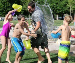 lapsia ja aikuinen pelaamassa vesisotaa