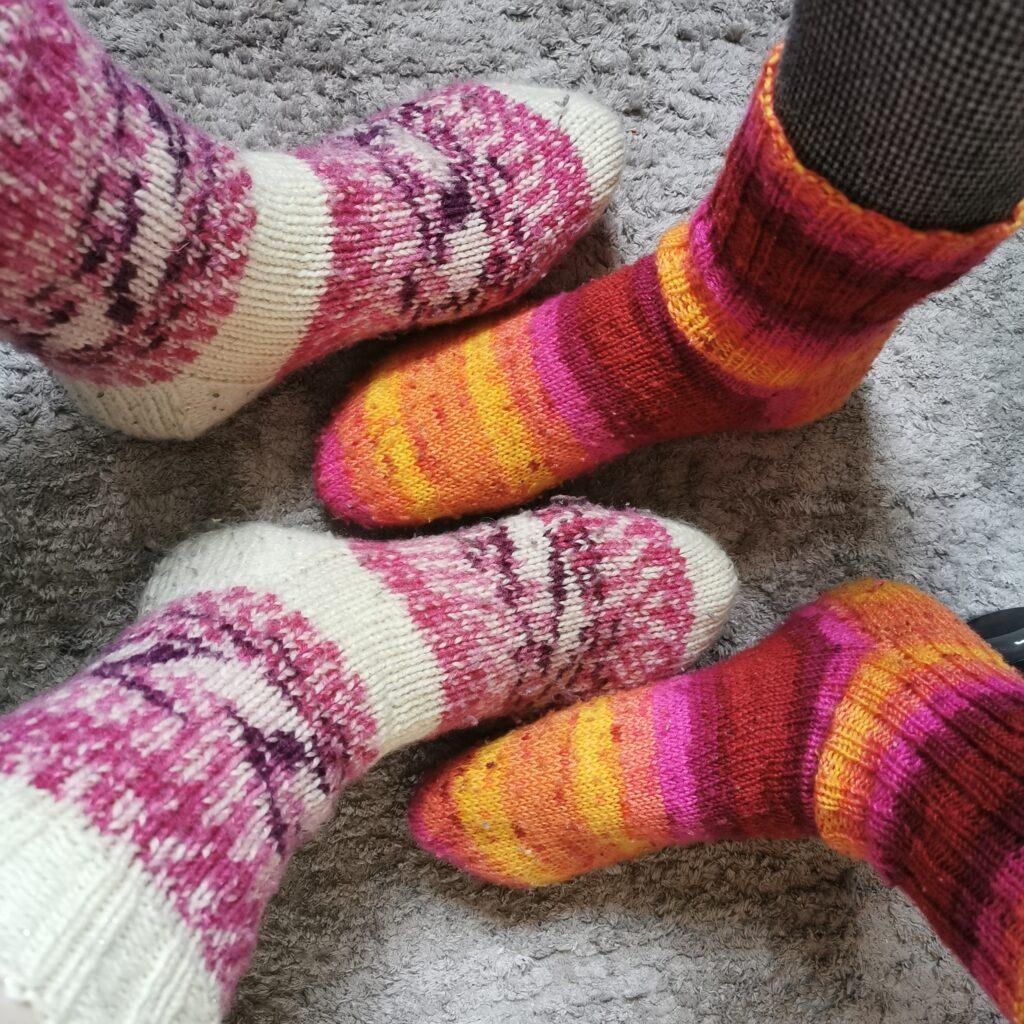 Kaksi paria jalkoja joissa villasukat.