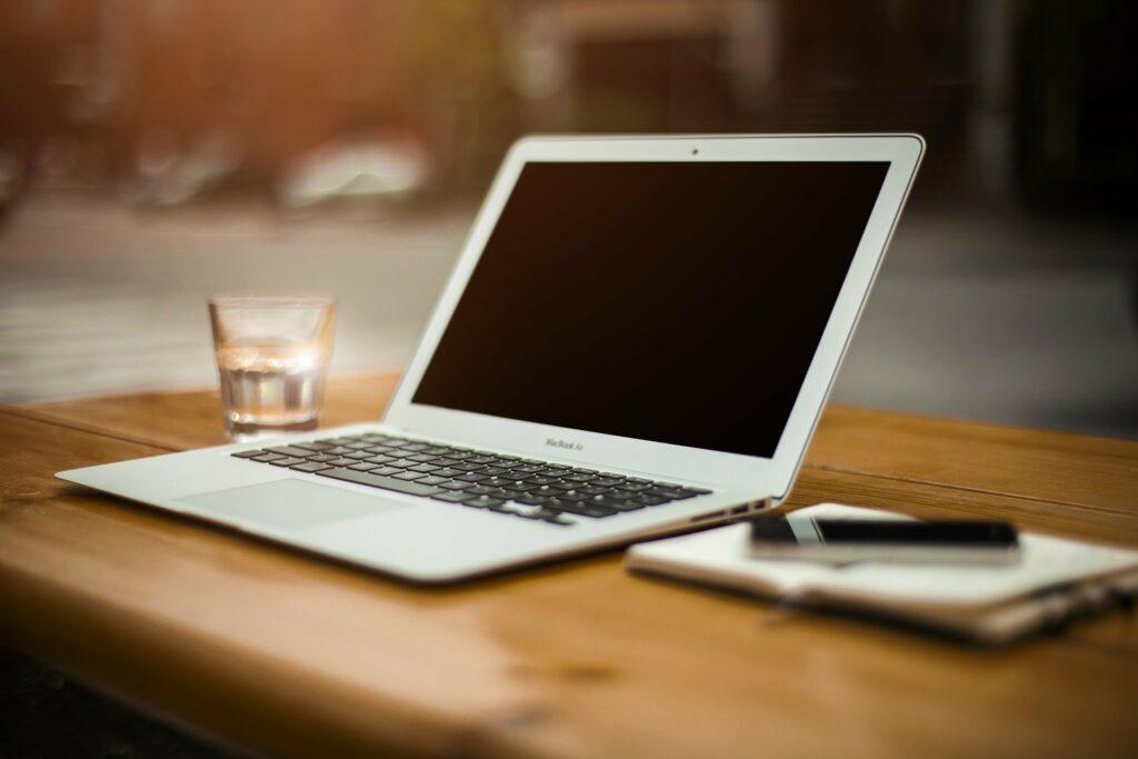 Kannettava tietokone pöydällä vesilasin ja muistiinpanovihkon kanssa.