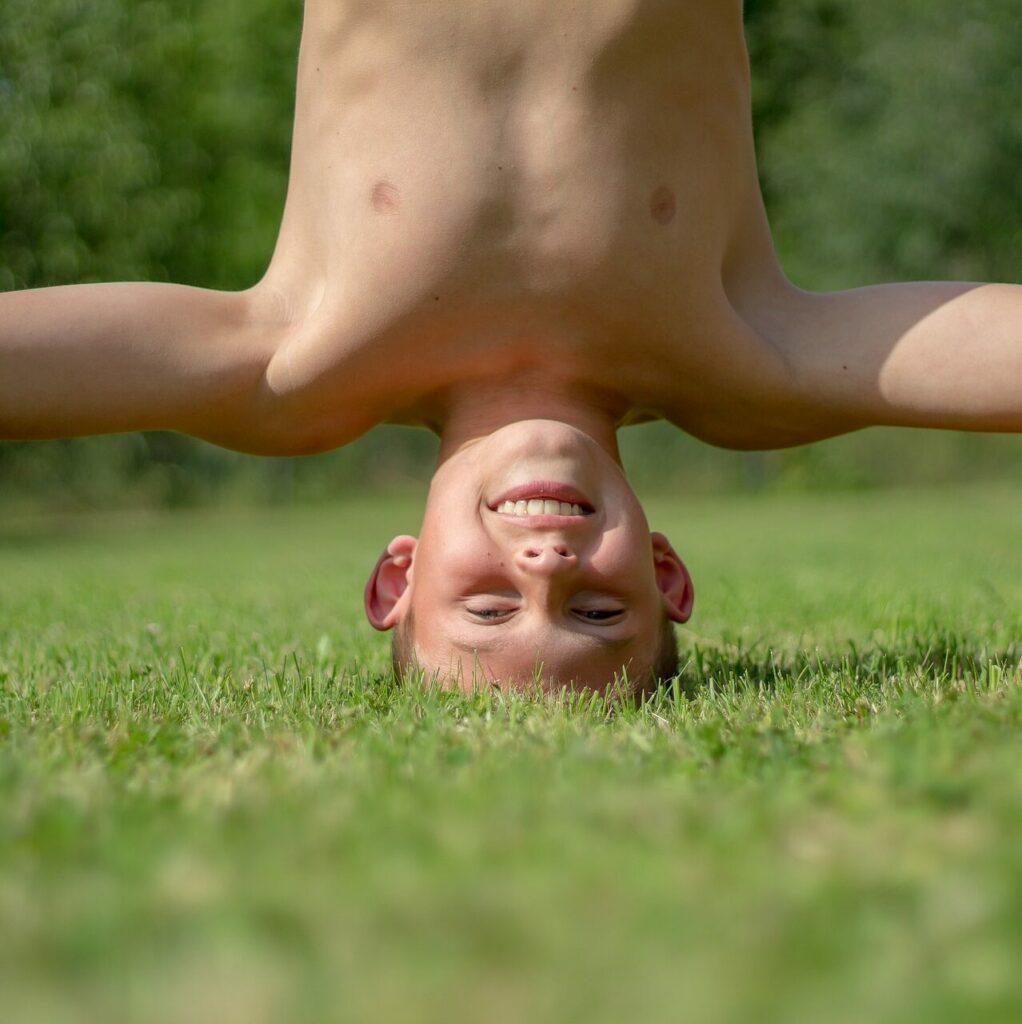 Lapsi seisoo päällään nurmikolla.
