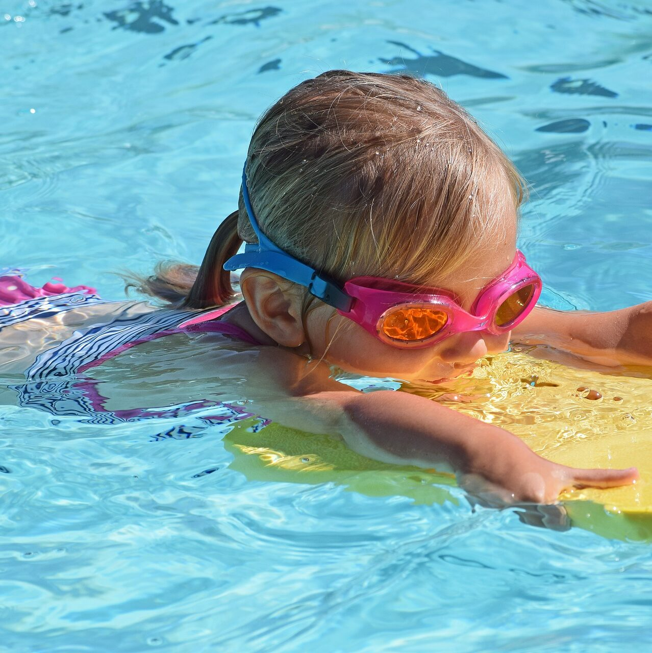 Pieni lapsi uimalasit päässä altaalla.